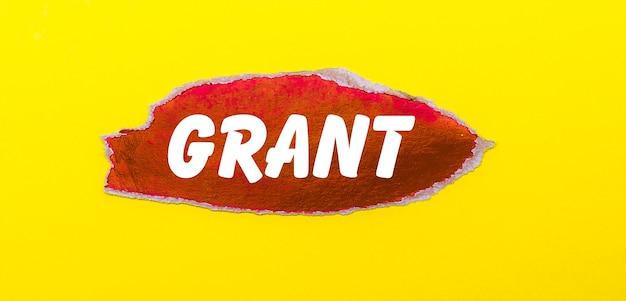 Na żółtej powierzchni arkusz czerwonego papieru z napisem grant