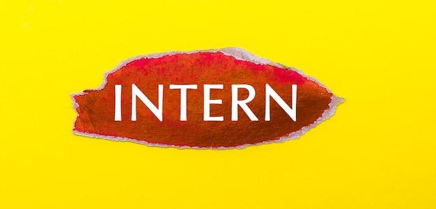 Na żółtej powierzchni kartka czerwonego papieru z napisem intern