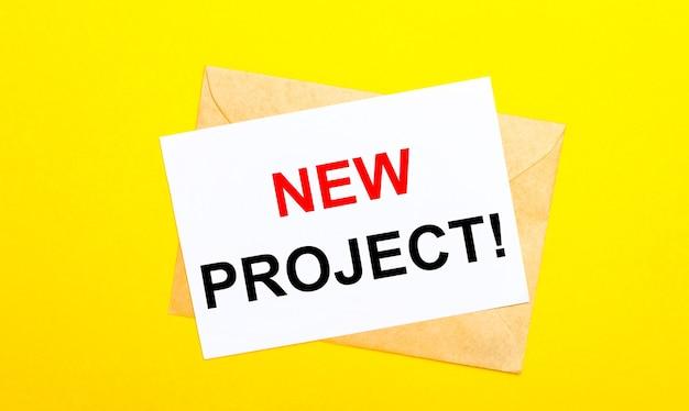 Na żółtej powierzchni koperta i kartka z napisem nowy projekt
