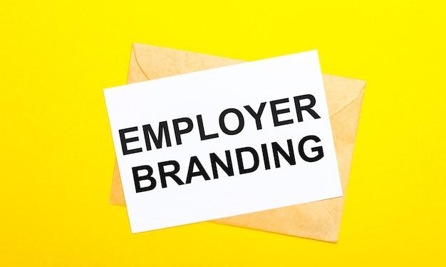 Na żółtej powierzchni koperta i kartka z napisem pracodawca branding