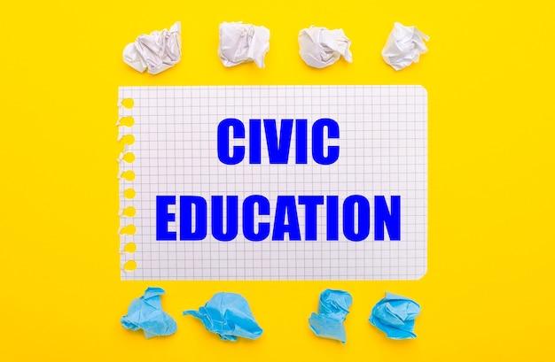 Na żółtym tle biało-niebieskie zmięte kartki oraz notes z napisem edukacja obywatelska.