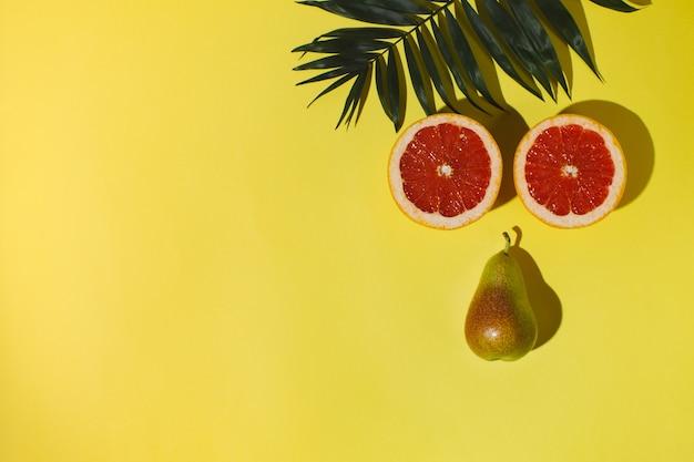 Na żółtym tle leży gałązka palmowa, grejpfrut i pokrojona na pół gruszka.