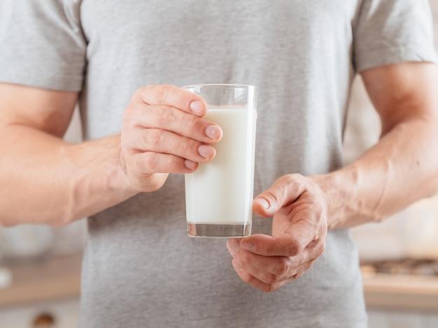 Nabiał. zbilansowane odżywianie. przycięte strzał człowieka trzymającego szklankę mleka sojowego.