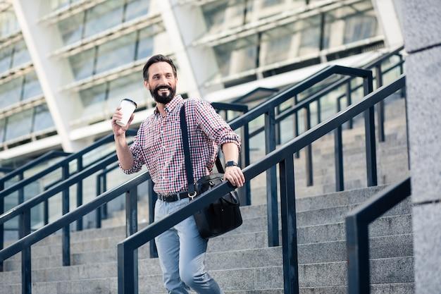 Nabierz trochę energii. pozytywny dorosły człowiek pije kawę idąc po schodach
