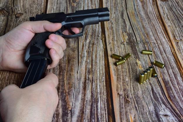 Naboje traumatyczne są rozrzucone na brązowym drewnianym tle. ręce trzymają magazynek pistoletu i pistolet