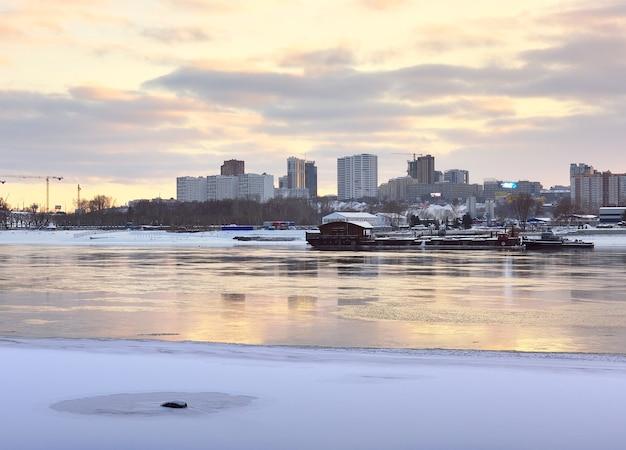 Nabrzeże rzeki ob w nowosybirsku zimowy wieczór nad terenem miasta pod złotym niebem
