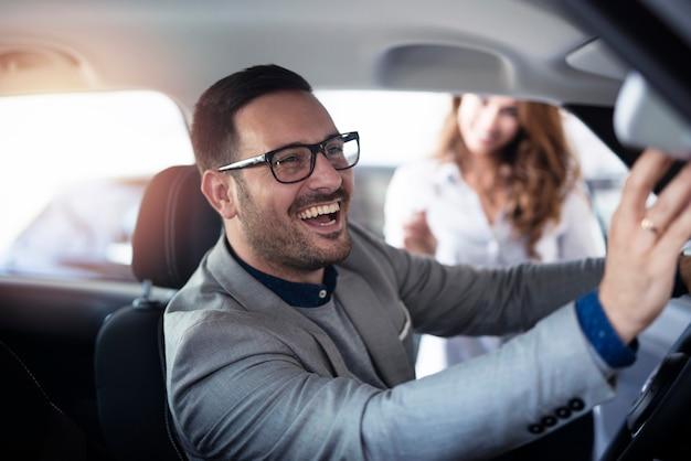 Nabywca samochodu lubiący nowe wnętrze pojazdu w salonie samochodowym