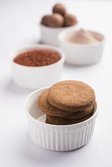 Nachni lub ragi laddu i herbatniki lub ciasteczka zrobione z prosa, cukru i ghee. to zdrowa żywność z indii. podawana w misce lub na talerzu z surową całością i proszkiem