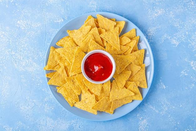 Nachos, chipsy kukurydziane z tortilli z ostrym sosem