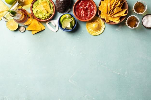 Nachos, guacamole, salsa, piwo i tequila na niebieskim tle