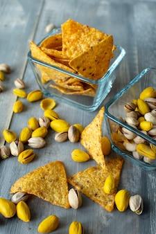 Nachos i pistacje słone i żółte z szafranem, przekąski w kwadratowych szklanych talerzach