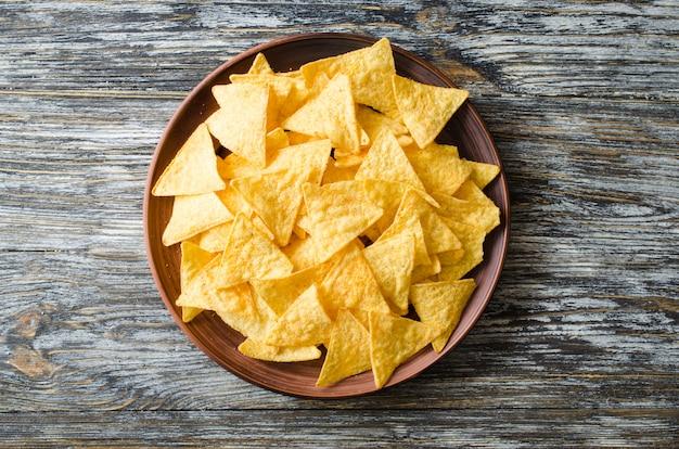 Nachos kukurydzani układy scaleni w talerzu na drewnianym stole. meksykańska koncepcja żywności.