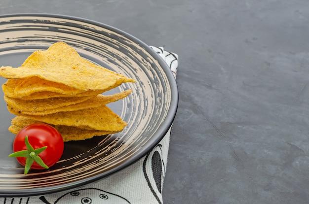 Nachos na czarnym talerzu i pomidor cherry w ciemnym stole. kuchnia meksykańska. zbliżenie. z miejsca na kopię.
