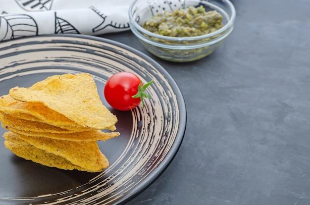 Nachos na czarnym talerzu z guacamole i sosem pomidorowym cherry na stole.