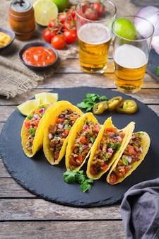Nachos nachos z tortilli kukurydzianej w skorupkach taco z mieloną wołowiną, mielonym mięsem, guacamole, salsą red hot jalapeno chili i sosem serowym z tequilą lub piwem na stole.