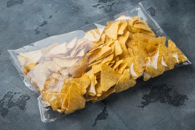 Nachos, trójkątne tradycyjne meksykańskie opakowanie przystawek kukurydzianych, na szarym stole