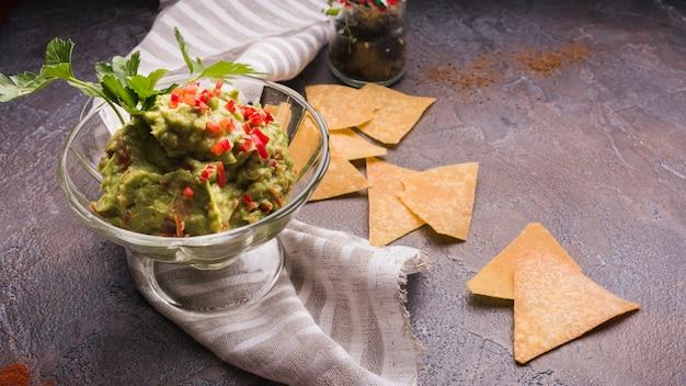 Nachos w pobliżu guacamole w szklanej misce i serwetce