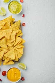 Nachos z chipsami z tortilli kukurydzianej i sosem dip, na białym stole, widok z góry lub flat lay
