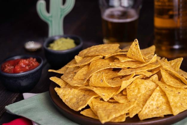 Nachos z guacamole i czerwonymi sosami chili na drewnianym stole. tło kuchni meksykańskiej