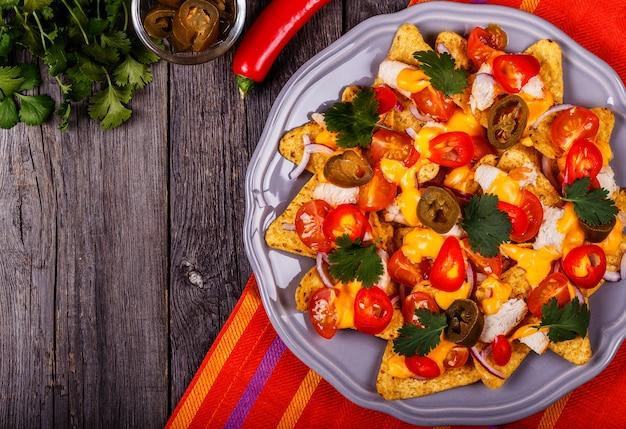 Nachos z topionym sosem serowym, jalapeno, kurczakiem i warzywami.