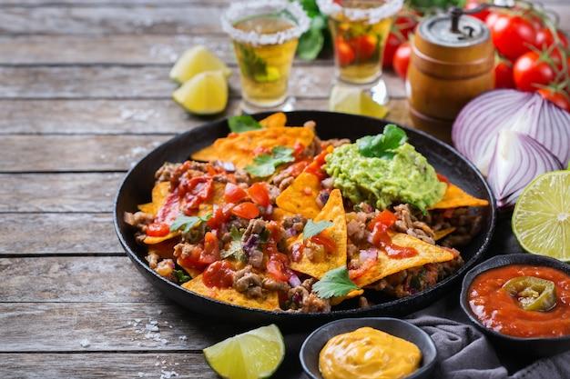 Nachos z żółtej tortilli kukurydzianej z mieloną wołowiną, mielonym mięsem, guacamole, salsą chili z papryczką jalapeno i sosem serowym z tequilą na drewnianym stole.