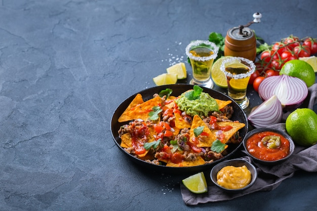 Nachos z żółtej tortilli kukurydzianej z mieloną wołowiną, mielonym mięsem mielonym, guacamole, salsą chili z jalapeno na gorąco i sosem serowym z tequilą na ciemnym stole. skopiuj tło przestrzeni