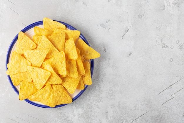 Nachosy kukurydziane w talerzu na szarym tle poziomo