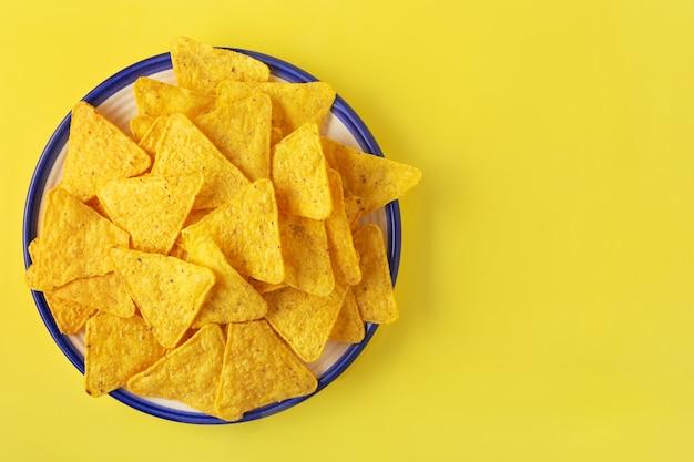 Nachosy kukurydziane w talerzu na żółtym tle poziomo