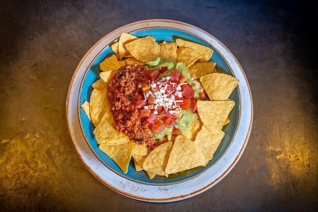 Nachosy z guacamole i sosem pomidorowym na czarnym tle, na niebieskim talerzu