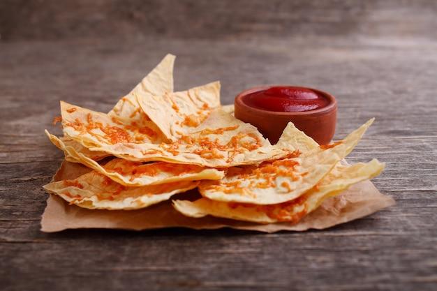 Nachosy z sosem pomidorowym na ciemnym drewnianym tle. koncepcja kuchni meksykańskiej, nachos.