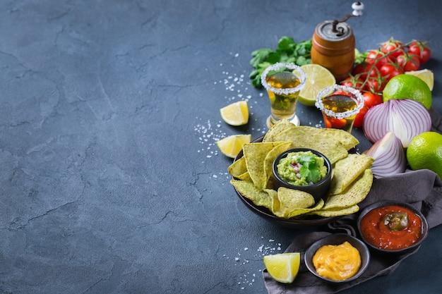 Nachosy z żółtej tortilli kukurydzianej z guacamole, salsą chili z papryczką jalapeno i sosem serowym z tequilą na ciemnym stole. skopiuj tło przestrzeni