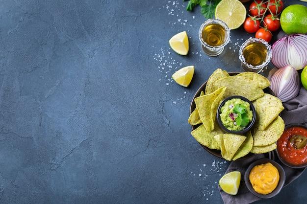 Nachosy z żółtej tortilli kukurydzianej z guacamole, salsą chili z papryczką jalapeno i sosem serowym z tequilą na ciemnym stole. widok z góry na płaskie tło z kopią tkankową