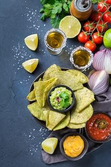 Nachosy z żółtej tortilli kukurydzianej z guacamole, salsą chili z papryczką jalapeno i sosem serowym z tequilą na ciemnym stole. widok z góry na płaskie tło