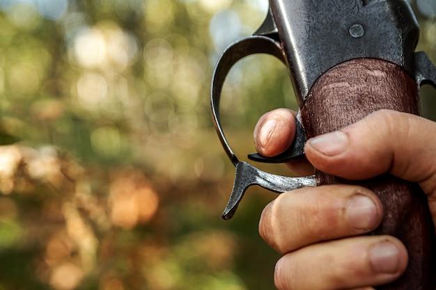 Naciśnij spust karabinu myśliwskiego w lesie jesienią