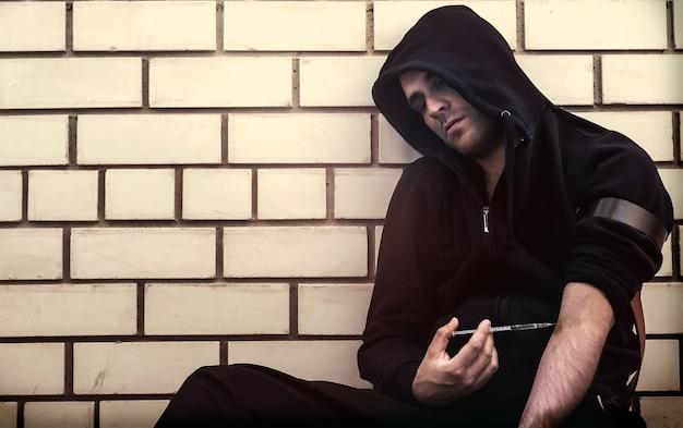 Naćpany narkotyk. uzależniony robi zastrzyk w żyłę dłonią małej strzykawki – czerpiąc z tego satysfakcję