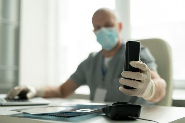 Naczelny chirurg w rękawiczkach siedzi przy biurku i korzysta z komputera podczas odbierania telefonu, skupiając się na dłoni