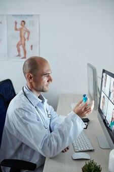 Naczelny lekarz szpitala odbywa konferencję online ze swoimi kolegami i omawia nową szczepionkę przeciwko koronawirusowi