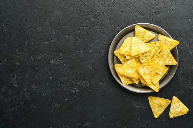 Naczosy. tradycyjne meksykańskie chipsy kukurydziane z ameryki łacińskiej z sosem guacamole w czarnej misce z awokado i dodatkami oraz kukurydzianymi nachosami. pasta z awokado. widok z góry. copyspace