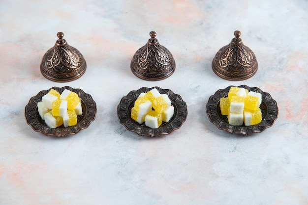 Naczynia candy i żółte cukierki z rzędu na białej powierzchni