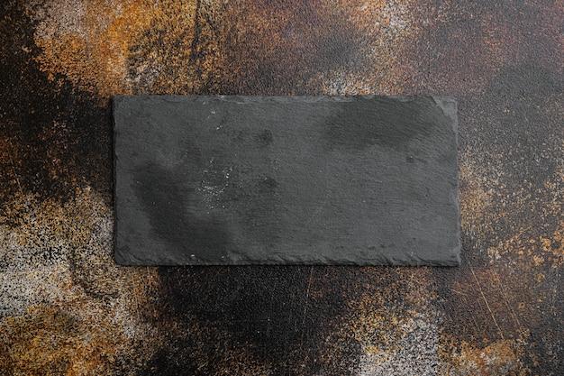 Naczynia do gotowania pusta kamienna deska do krojenia z kopią miejsca na tekst lub jedzenie z kopią miejsca na tekst lub jedzenie, widok z góry płasko leżał, na starym ciemnym, rustykalnym tle stołu