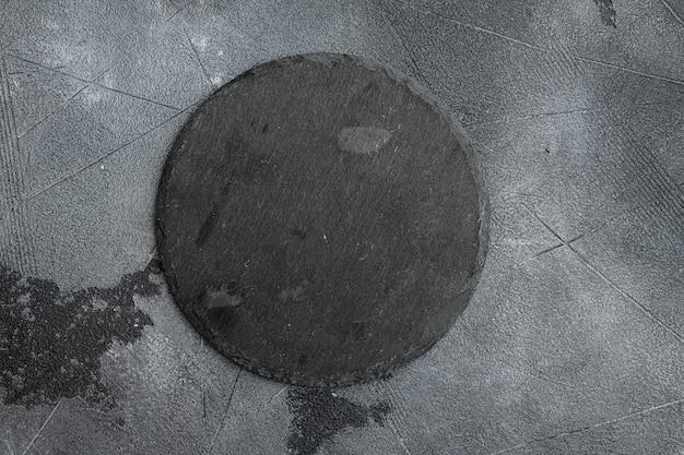 Naczynia do gotowania pusta kamienna deska do krojenia z kopią miejsca na tekst lub jedzenie z kopią miejsca na tekst lub jedzenie, widok z góry płasko leżał, na szarym tle stołu z kamienia