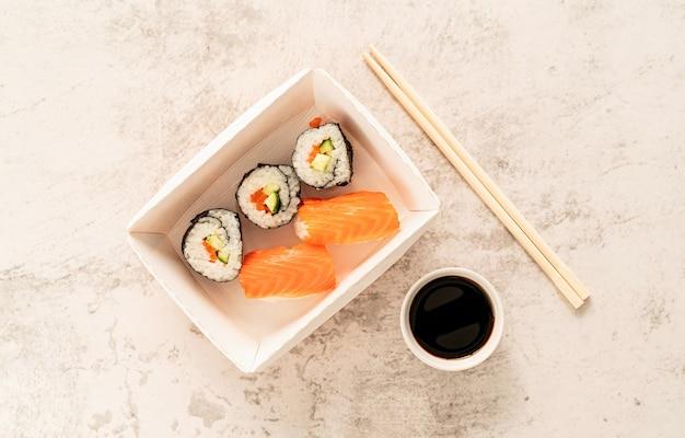 Naczynia jednorazowe, opakowanie zero waste. zestaw sushi w papierowym pudełku z sosem sojowym i pałeczkami