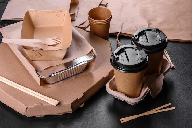 Naczynia jednorazowe wykonane z przyjaznego dla środowiska brązowego kartonu na ciemnym tle. dostawa żywności w naczyniach jednorazowych
