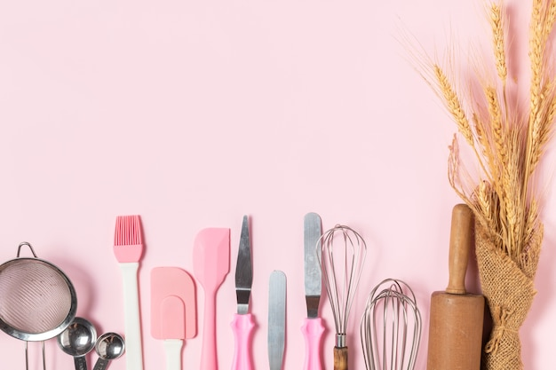 Naczynia kuchenne do wypieków na różowym tle,
