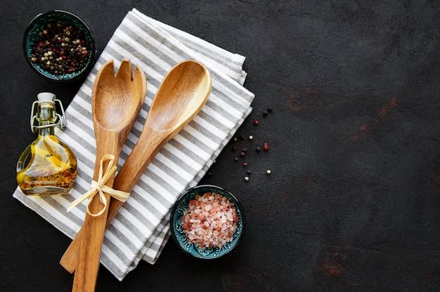 Naczynia kuchenne drewniane sztućce i przyprawy na czarnym tle