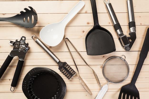 Naczynia kuchenne i akcesoria na drewnianym stole.