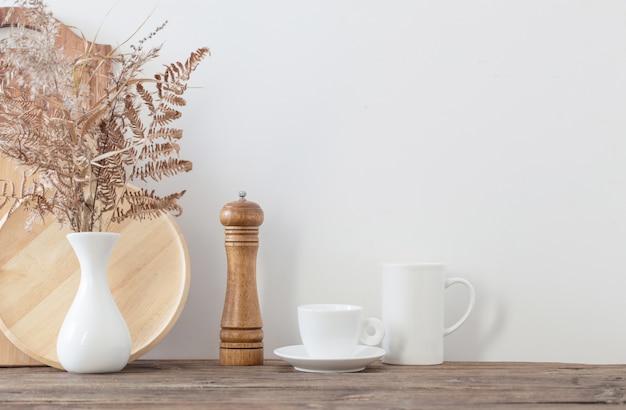 Naczynia kuchenne na drewnianej półce w białej kuchni