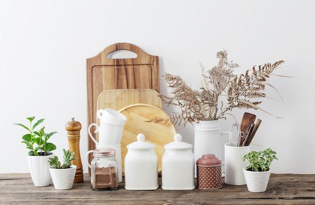 Naczynia kuchenne na drewnianym stole w białej kuchni