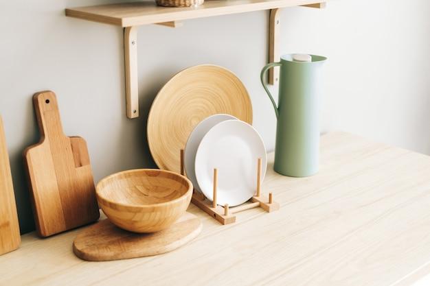 Naczynia kuchenne na drewnianym stole w nowoczesnej jasnej kuchni