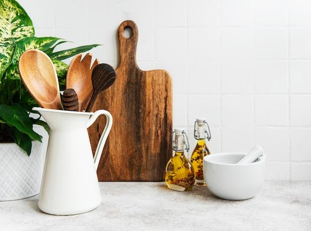 Naczynia kuchenne, narzędzia i naczynia na tle ściany białe płytki. wnętrze, nowoczesna kuchnia w jasnych kolorach. puste miejsce na tekst, widok z przodu